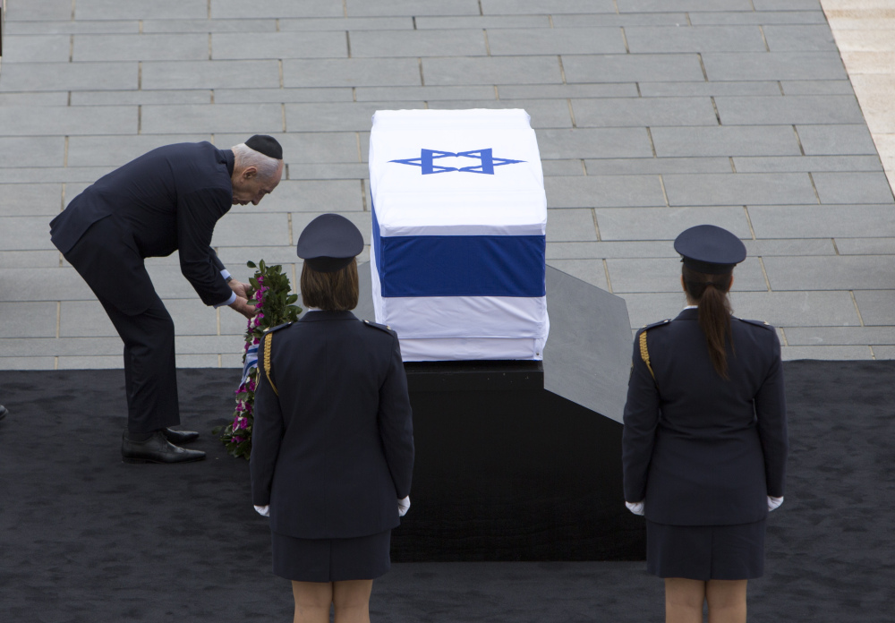 Israeli President Shimon Peres lays a wreath on the coffin of former Israeli Prime Minister Ariel Sharon at the Knesset plaza, in Jerusalem on Sunday.