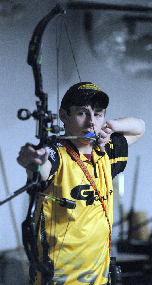 SHOOTING PRACTICE: Charlie Weinstein, 17, practices archery on Thursday in a storage room at Maranacook Community Middle School in Readfield.