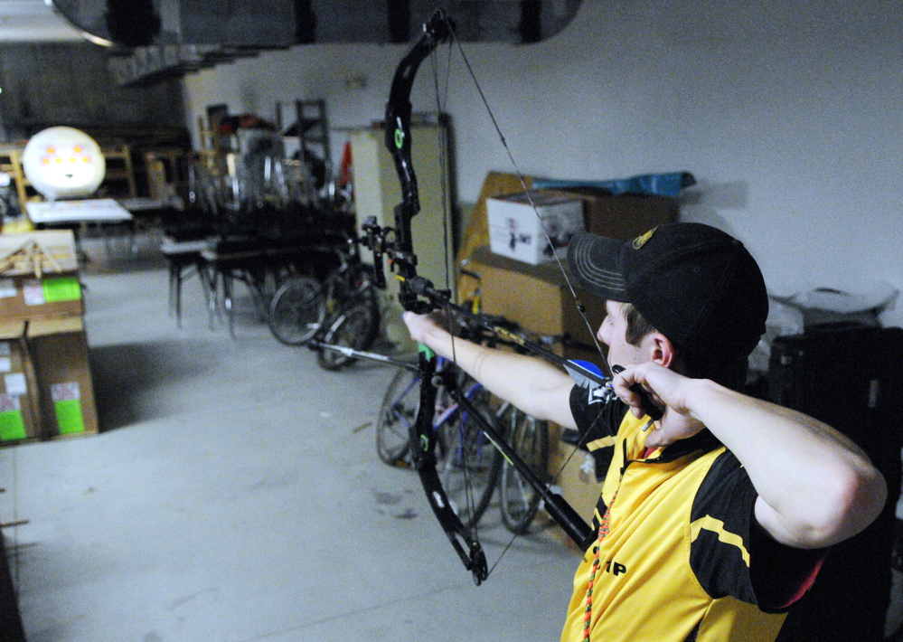 On Target: Charlie Weinstein, 17, shoots at a target 18 meters (about 59 feet) away on Thursday in a storage room at Maranacook Community Middle School in Readfield.