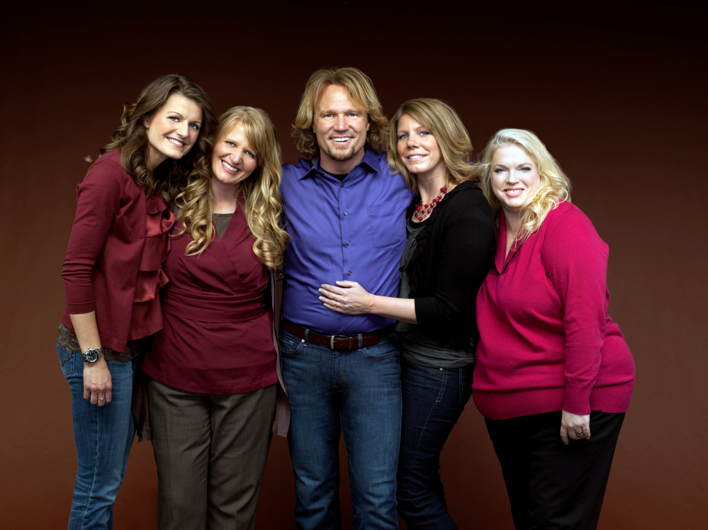 """Kody Brown, center, poses with his wives, from left, Robyn, Christine, Meri and Janelle, in a promotional photo for the reality series, """"Sister Wives,"""" which aired in March 2011. When the polygamous family learned in December 2013 that a federal judge in Utah struck down key parts of the state's polygamy laws, Brown and his four wives said they cried and felt deeply emotional."""