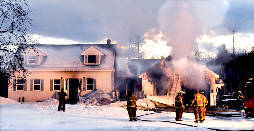 HOUSE FIRE: Homeowner Clayton Williams, at left, watches as smoke billows from the rear of his home two hours after the fire started around 3 p.m. Williams said no one was injured and his wife and two dogs got out safely, but the garage and two vehicles were destroyed, and the house received extensive damage.