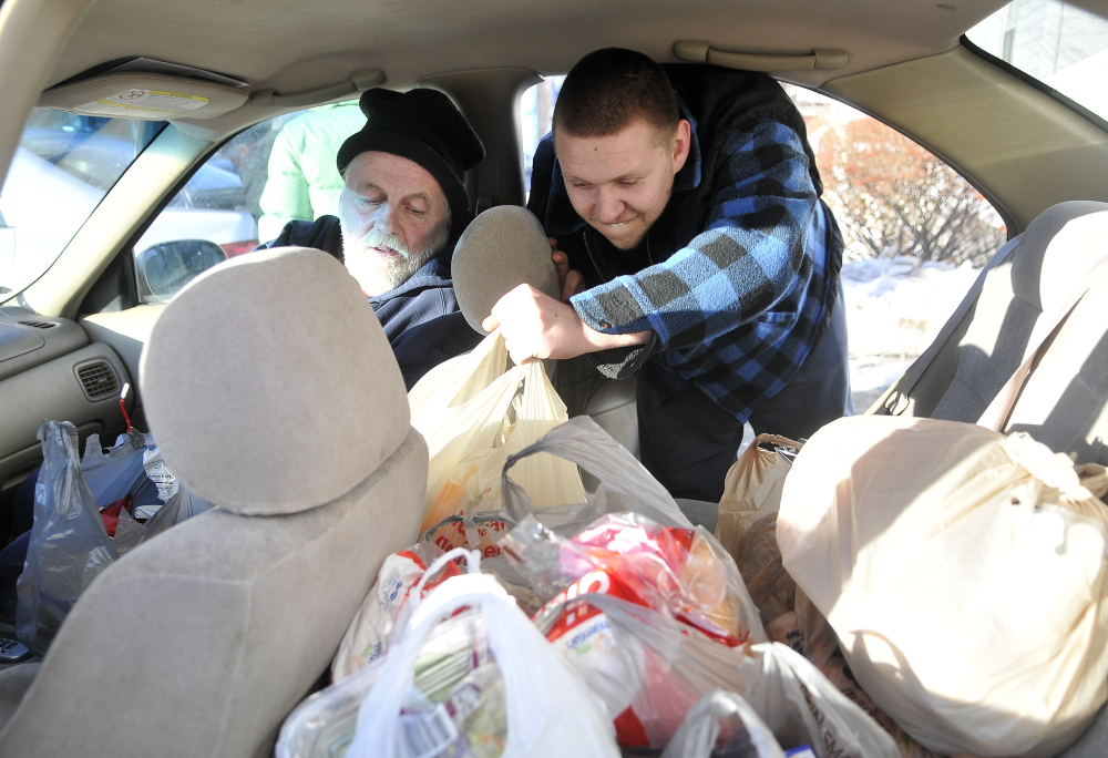 Volunteer Work: Sam Young, 19, loads bags of food in to the back seat of Joe Lessard's car with Dale Heald, 53, in the front seat at the First Baptist Church food pantry in Fairfield on Thursday.