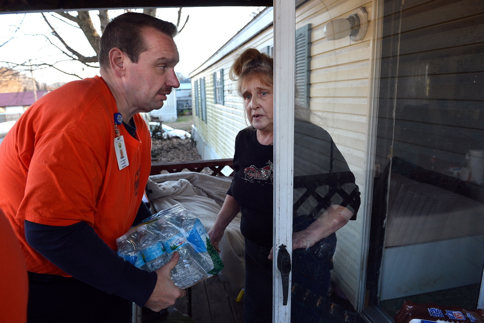 JoAnn Chapouris asks paramedic John Johnson to carry a case of water inside her home in Rand, W.Va., on Sunday.