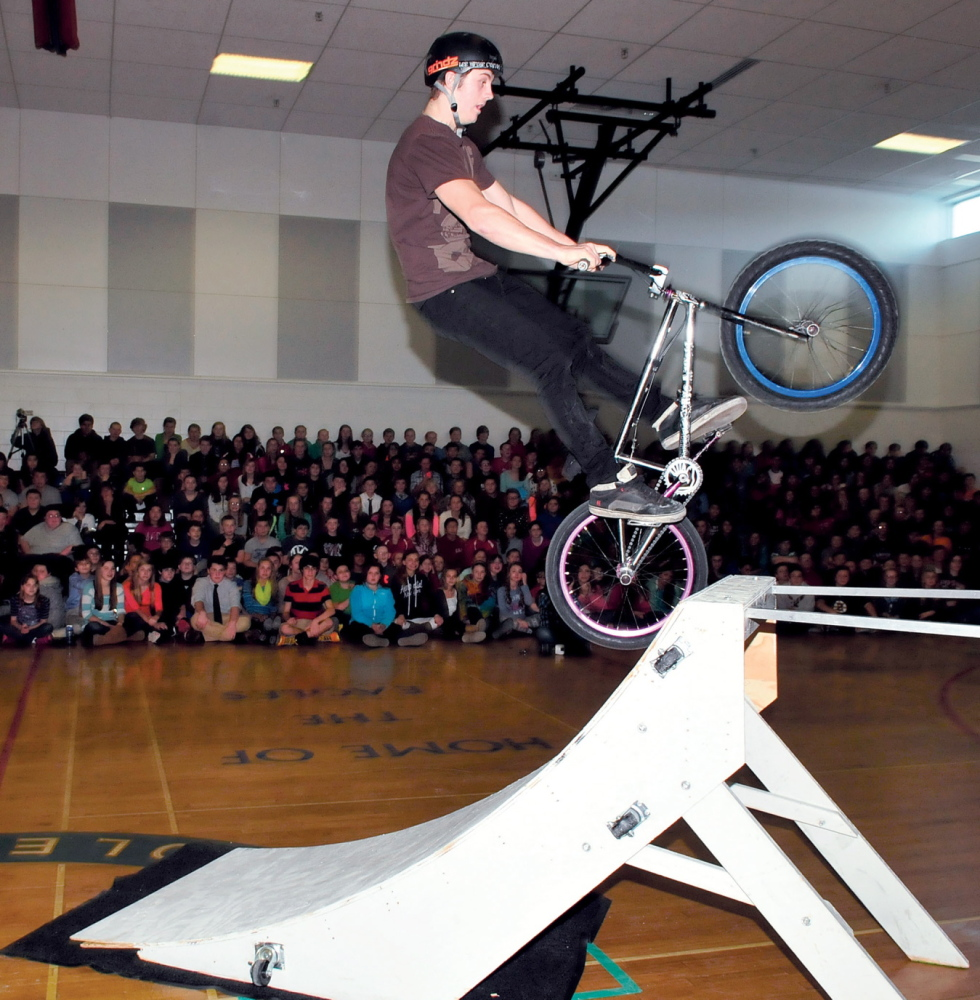 UP BEAT MESSAGE: Ian Bradley rides his bike up a ramp in one of the eye-catching demonstrations that was part of the Bullying Prevention and Living a Positive Lifestyle presentation at Messalonskee Middle School in Oakland on Monday.