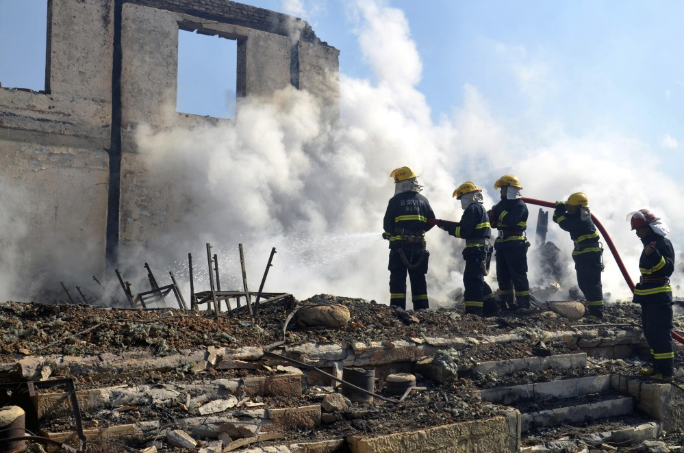 Firefighters put out embers Saturday at the ancient town of Dukezong in Shangri-la, a resort county in southwest China's Yunnan province.