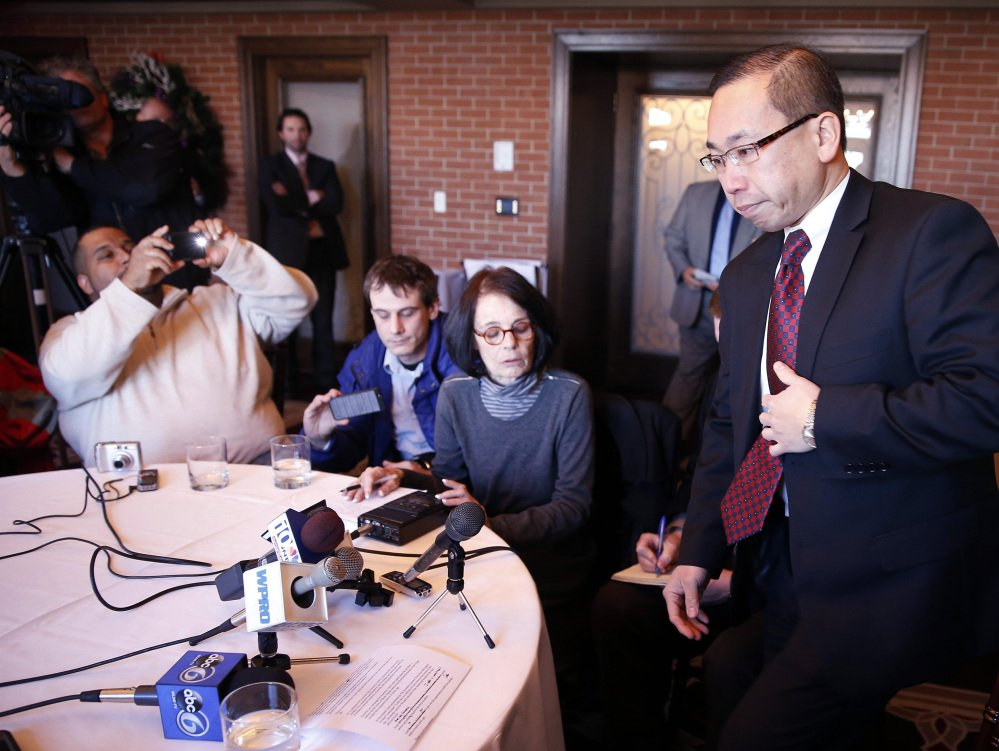 Cranston, R.I., Mayor Allan Fung, right, takes his seat after briefly stepping out of the room during a news conference Monday.