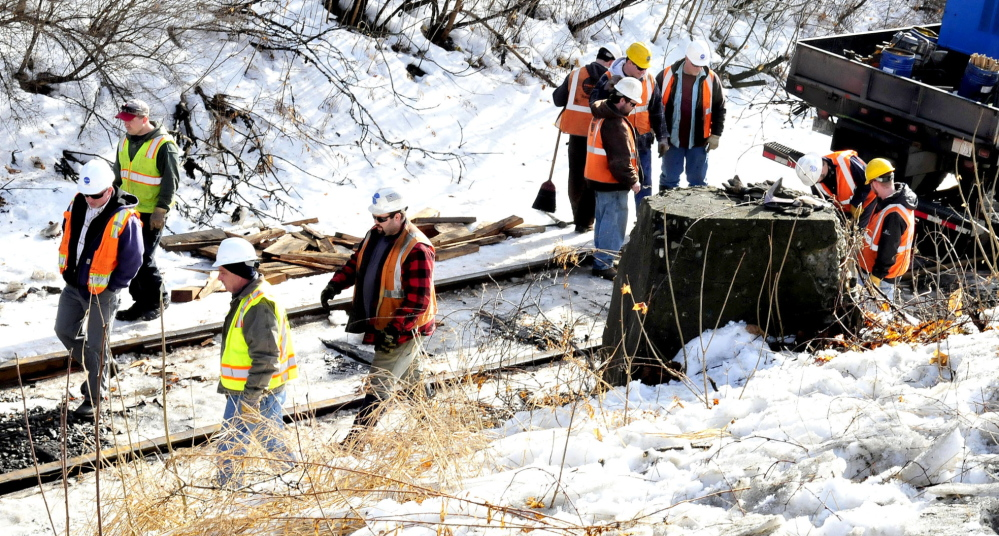 RAIL FIX: Workers with Pan Am Railways work on the twisted rail along Bay Street in Winslow on Wednesday. At least one railroad car has been listing to the side since Tuesday evening.