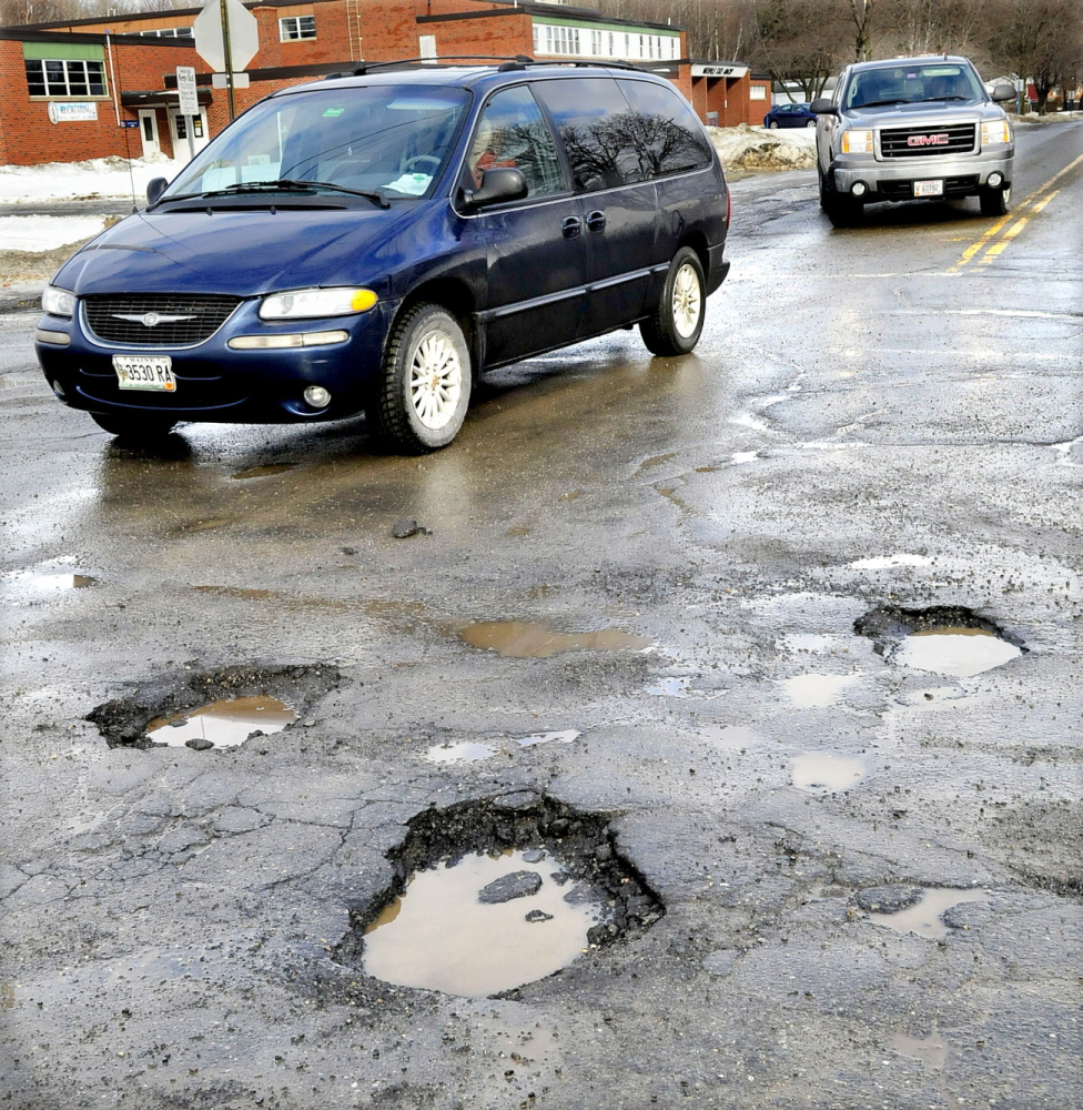 ROUGH RIDE: Motorists have to dodge numerous potholes at the busy intersection of Drummond Avenue and the Armory Road in Waterville on Wednesday.