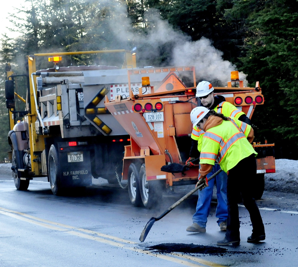 STEAMED: Steam rises from warm asphalt as Maine Department of Transportation employees Deven Moon and Tina Gilbert fill some of the numerous potholes on the Unity Road in Benton on Wednesday.