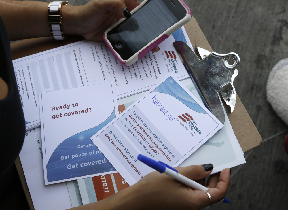 A field organizer with Enroll America holds a clipboard with pamphlets encouraging people to sign up for health care offered by the Affordable Care Act. The House on Thursday passed a bill requiring the administration to report weekly, rather than monthly, on sign-up numbers.