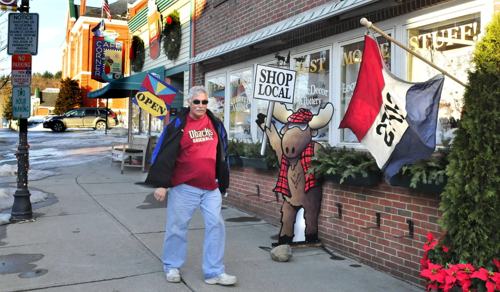 POPULAR SPOT: Chris Giemza walks past popular businesses Java Joes and Mooseville in downtown Farmington this week. Town officials are hoping new initiatives, including prochures and a proposed economic development committee, will bring new businesses and residents to town.