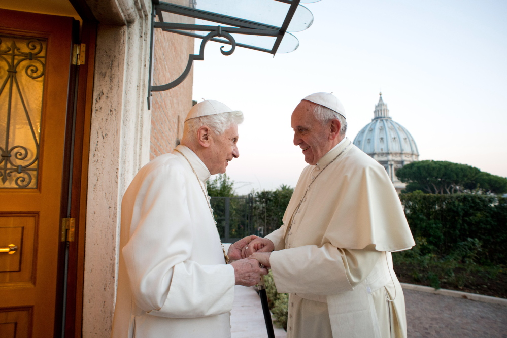 In this picture provided by the Vatican newspaper L'Osservatore Romano, Pope Emeritus Benedict XVI, left, welcomes Pope Francis as they exchanged Christmas greetings, at the Vatican on Dec. 23, 2013.