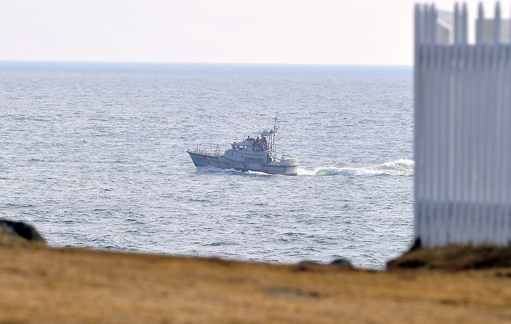 A Coast Guard boat cruises by Pemaquid Point, where searchers looked for survivors after receiving a report of a sailboat sinking.