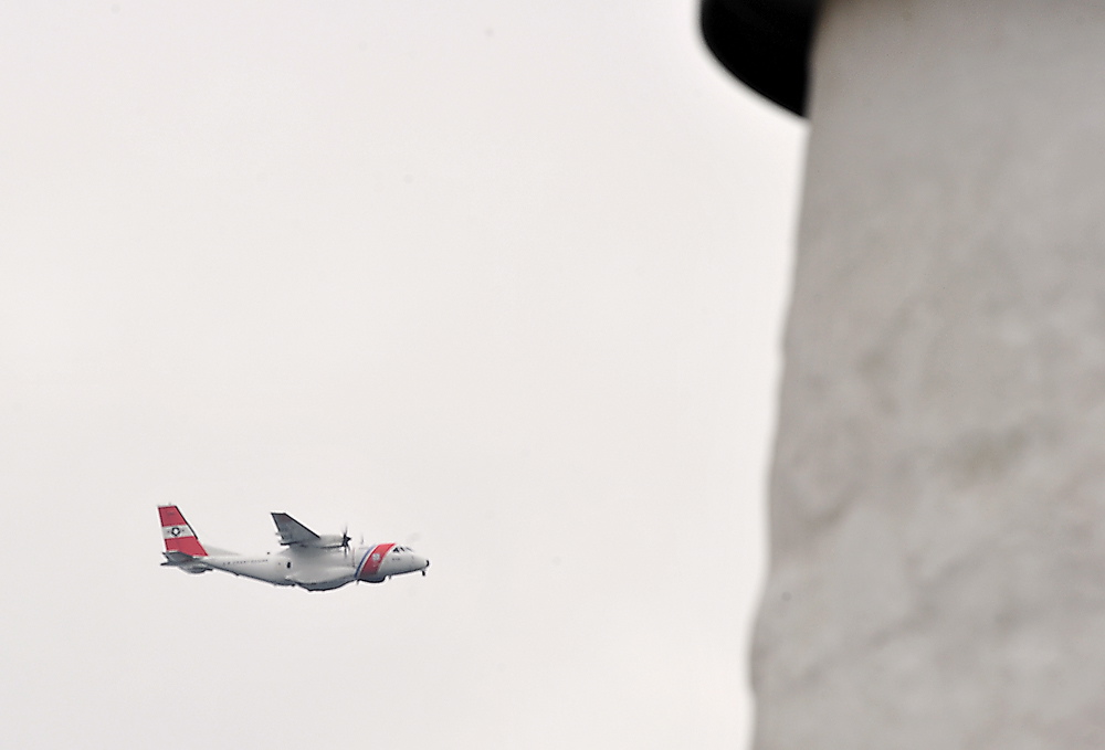 A Coast Guard plane flies by Pemaquid Point lighthouse to help search for survivors of a reported sailboat sinking Friday. The search for the vessel was suspended Friday afternoon.