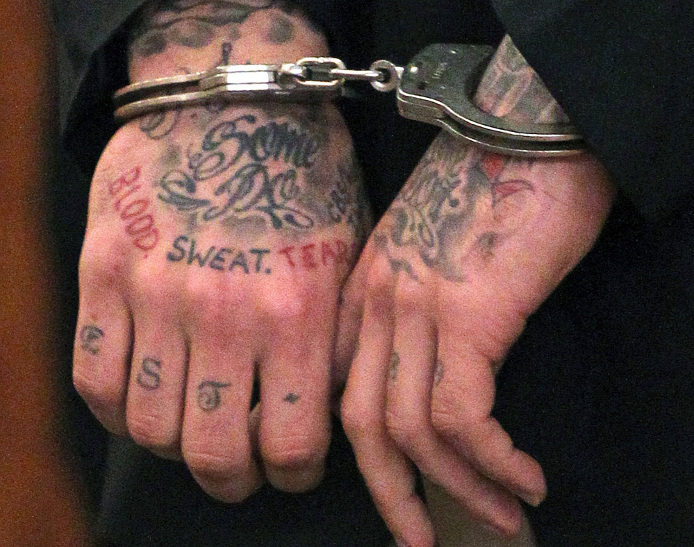 Former New England Patriots player Aaron Hernandez's tattooed hands are secured with handcuffs in this Dec. 23, 2013, photo.