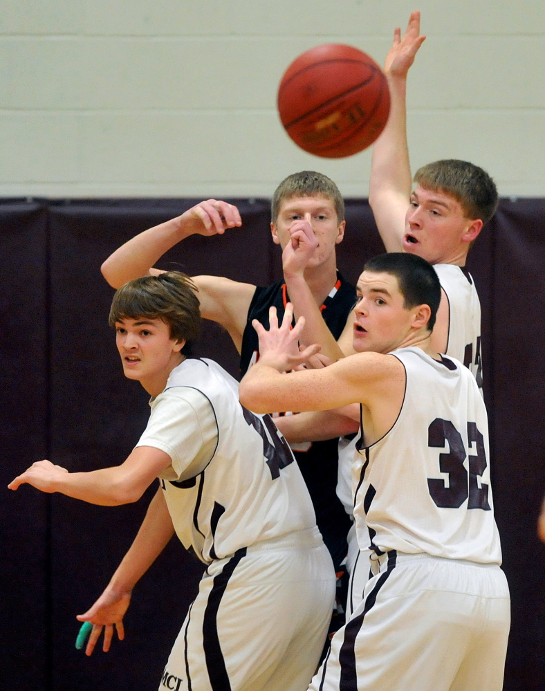 Staff photo by Michael G. Seamans Winslow High School's Justin Martin, 30, center facing, passes the ball out to teammate Justin Kervin, 15, as he is triple teamed by Maine Central Institute defenders in Pittsfield on Friday.