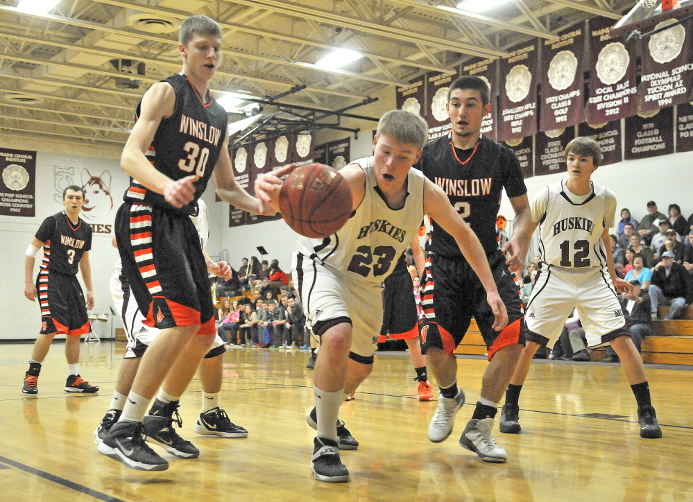 Staff photo by Michael G. Seamans Maine Central Institute's Mitchell Hallee, 23, center, fights for the loose ball with Winslow High School's Nason Lanphier, 2, right, and Justin Martin, 30, left, in Pittsfield on Friday.