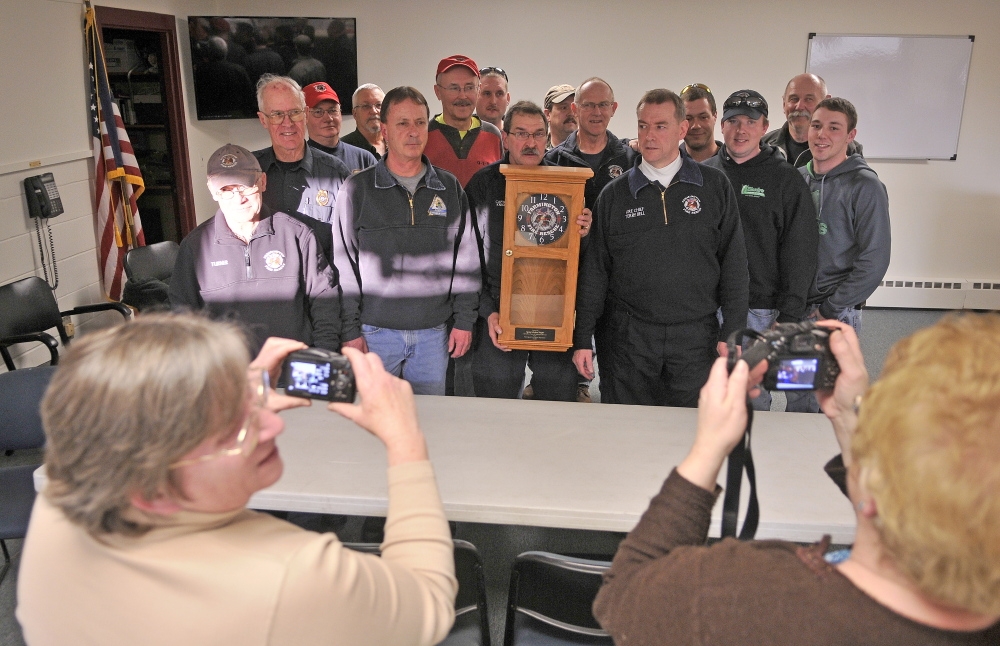 time to leave: Capt. Richard Knight, center, holds a clock given to him for his 35 years of service with the Farmington fire department at the station on Friday.