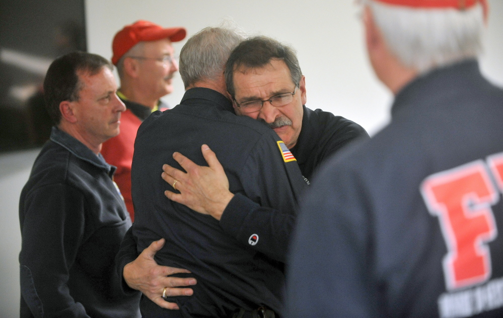 goodbye: Capt. Richard Knight, facing right center, hugs Clyde Ross at his retirement party at the Farmington fire station on Friday. Knight served the Farmington community as a firefighter for 35 years.