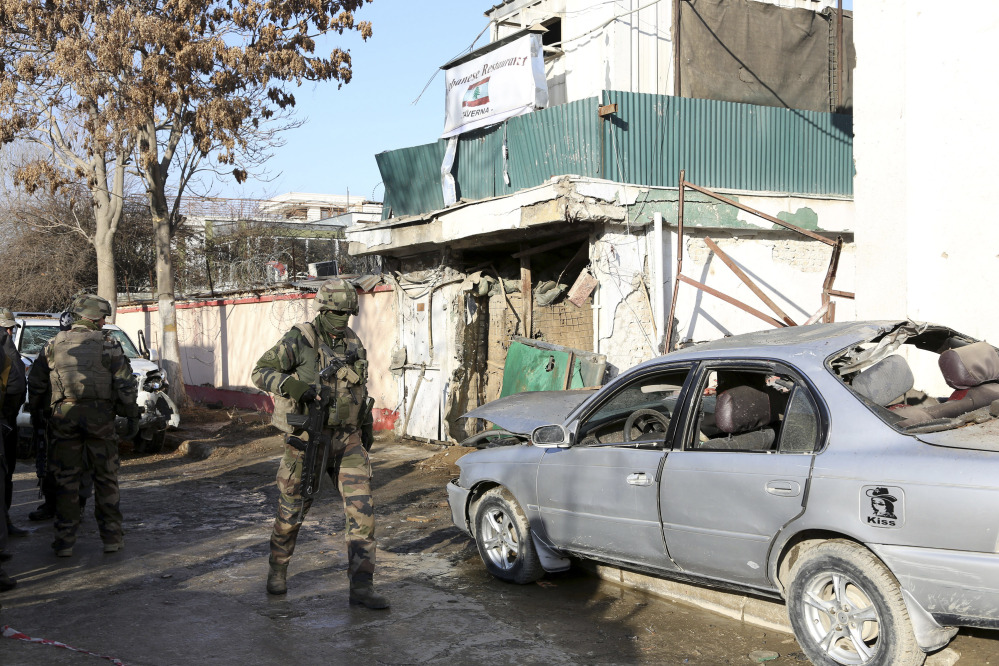 NATO International security assistance forces personnel investigate at the site of the Friday's suicide attack and shooting, in Kabul, Afghanistan, on Saturday. A Taliban suicide bomber and two gunmen on Friday attacked a Lebanese restaurant that is popular with foreigners and affluent Afghans in Kabul, a brazen attack that left 16 dead, including foreigners dining inside and two other gunmen, officials said.