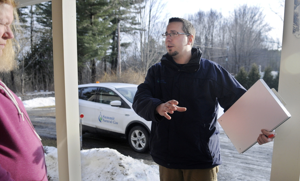 COLD CALL: Summit Natural Gas of Maine salesman Nick Snowdeal speaks Wednesday with Hallowell home owner Cindy Lockwood about the location of a distribution line the company is hoping to install near her home. The arrival in 2013 of natural gas firms installing underground pipes in the Kennebec Valley has strained the resources of communities and utilities.