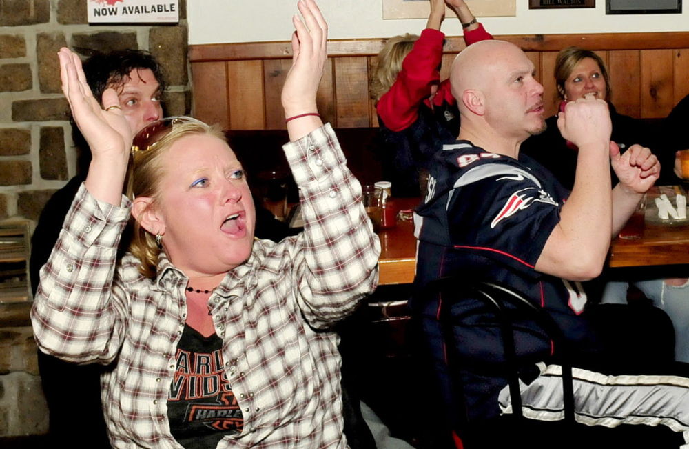 Staff photo by David Leaming GO PATS: New England Patriots fans celebrate a play during AFC championship game against Denver Broncos during first half action at the Pointe Afta restaurant in Winslow on Sunday, jan. 19, 2014. From left are Sammi-Jo MacFarland and Doug Dutton.