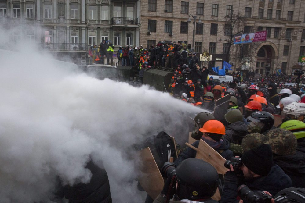 Protesters clash with riot police in central Kiev, Ukraine, on Sunday. Thousands of protesters clashed with riot police in the center of the Ukrainian capital, after the passage of harsh anti-protest legislation last week seen as part of attempts to quash anti-government demonstrations. A group of radical activists began attacking riot police with sticks, trying to push their way toward the Ukrainian parliament building, which has been cordoned off by rows of police and buses