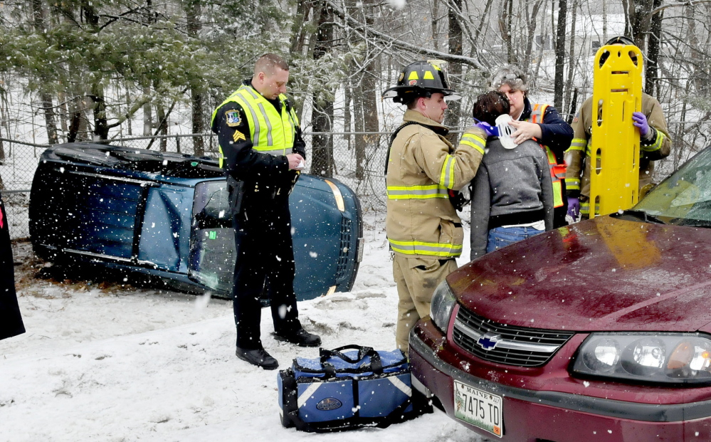 SUDDEN IMPACT: Waterville police officer Lincoln Ryder, left, and state police responded to a multi-vehicle rollover accident on the snow-covered exit ramp at mile 127 southbound on Interstate 95 in Waterville on Sunday. An occupant was taken to the hospital. There were reports of several other weather-related accidents on the highway during the storm.