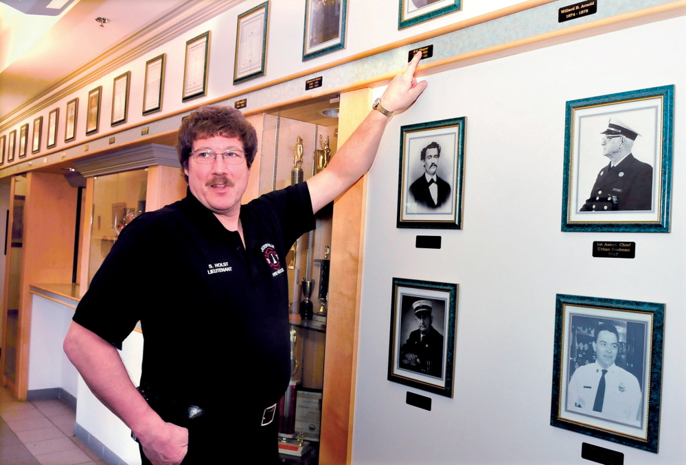 HISTORY BUFF: Waterville Fire Department Lt. Scott Holst speaks beside a wall of photographs of former fire chiefs recently. Holst is updating and expanding on a book documenting the history of the department.