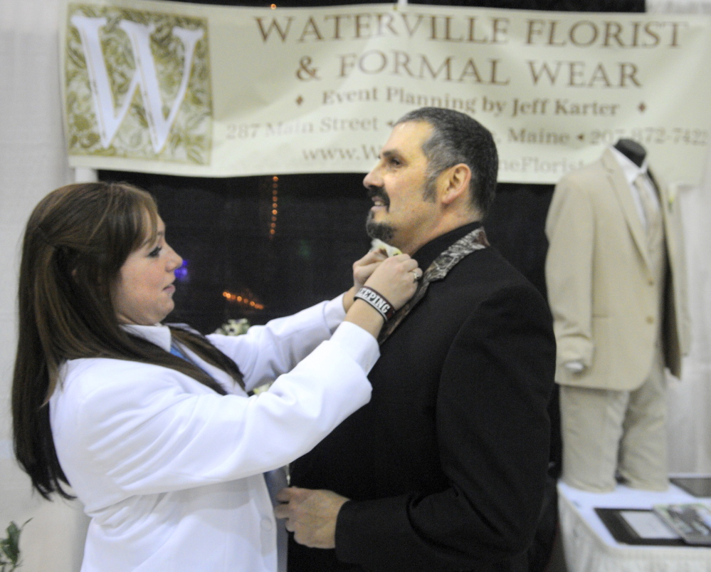 Preparing: Brandy Wyman secures Jeff Karter's bow tie Sunday at the booth for his business, Waterville Florist & Formal Wear, at the 22nd Annual Augusta Wedding Show at the Augusta Armory.
