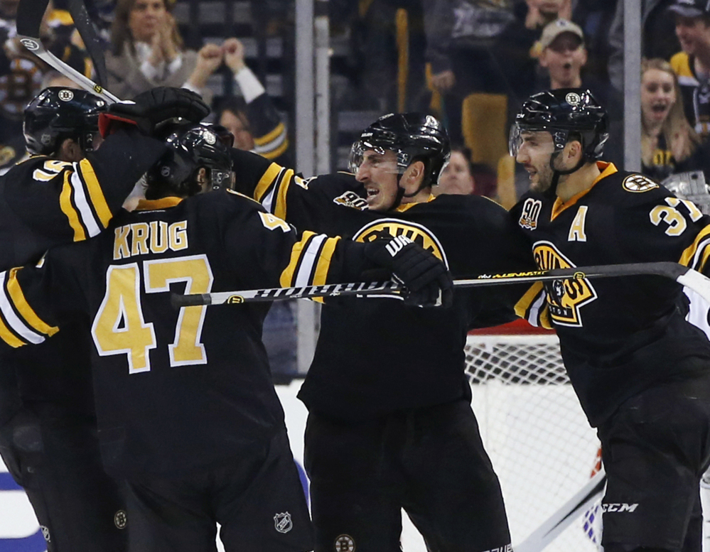Boston Bruins left wing Brad Marchand, center, celebrates his game-winning goal against the Los Angeles Kings with teammates Torey Krug (47) and Patrice Bergeron (37) during the third period of an NHL hockey game in Boston, Monday, Jan. 20, 2014. The Bruins won 3-2. (AP Photo/Elise Amendola)