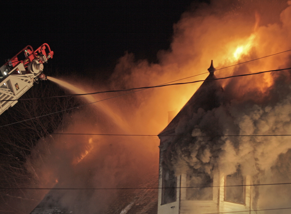 A Portland firefighter works atop a ladder to douse flames at an apartment at 84 Irving Street in Portland on Sunday night.