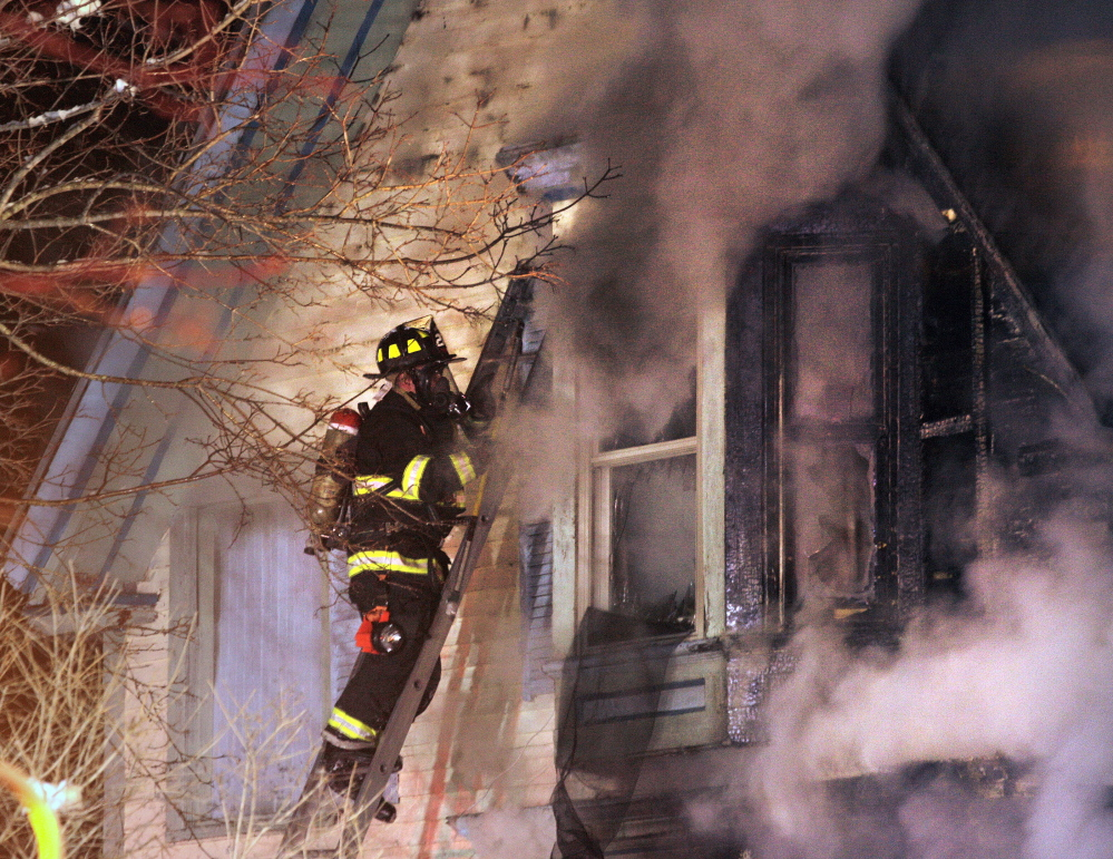 A firefighter battles a fire in an apartment house at 84 Irving St. in Portland Sunday night.