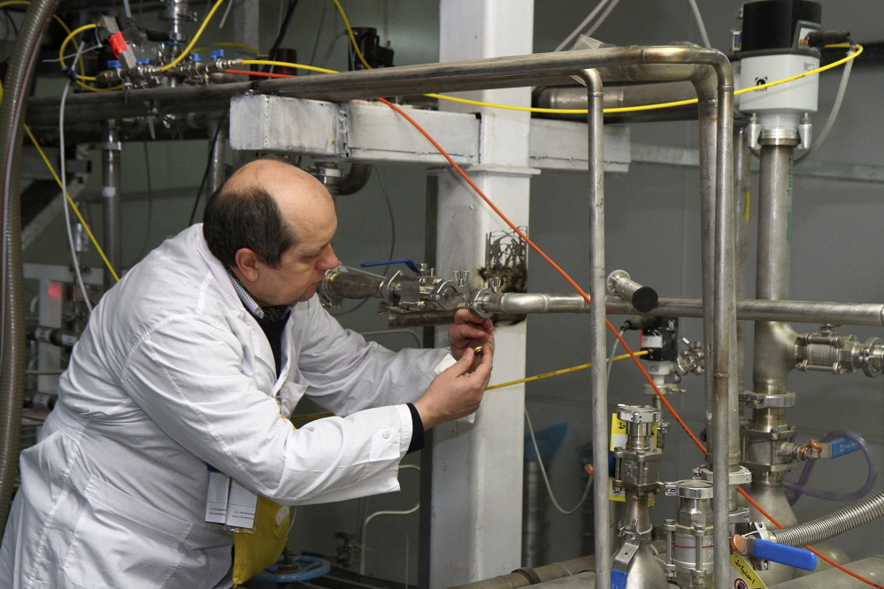 An unidentified International Atomic Energy Agency inspector cuts the connections between centrifuge cascades at the Natanz facility, some 200 miles south of Tehran, Iran, on Monday.