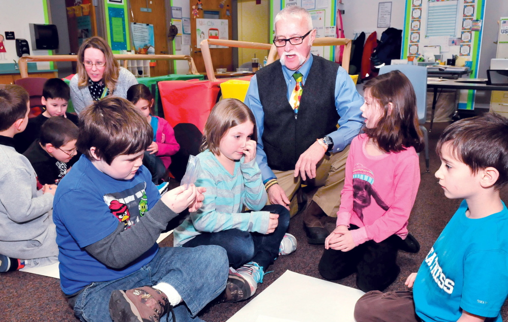 Staff photo by David Leaming YOUNG MERCHANTS: Jobs for Maine Graduates Director Victor Esposito helps Vassalboro Community School students learn about money management at the school on Thursday, Jan. 23, 2014. Also helping another group is parent Carrie Coombs. The program helps younger grades learn skills about money spending and budgets. Students from left are Eldon Thompson, Justine Harford, Lara Stinchfield and Gavin Rose.