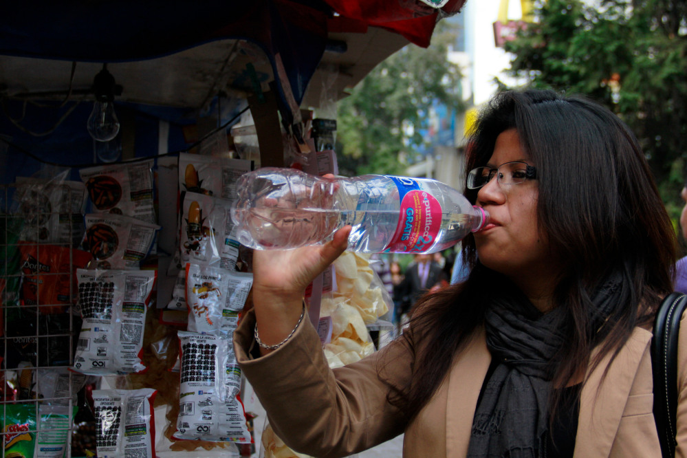 A woman drinks bottled water in Mexico City, where a law recently approved by the city's legislators will require all restaurants to install filters, offering patrons free, drinkable potable water that won't lead to stomach problems and other ailments.