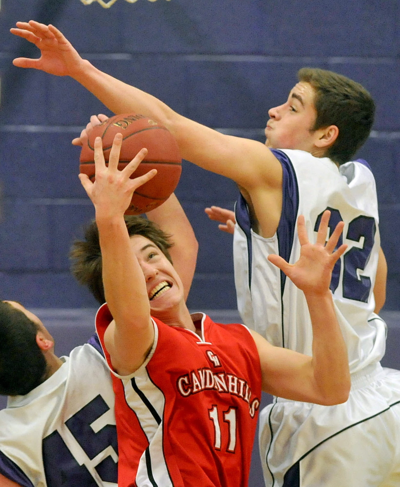 Staff photo by Michael G. Seamans Camden Hills High School's Chandler Crans, 11, center, fights for the loose ball with Waterville Senior High School's Benjamin Cox, 45, left, and Owen Brown, 32, in the third quarter in Waterville on Friday. Waterville defeated Camden Hills 62-56.