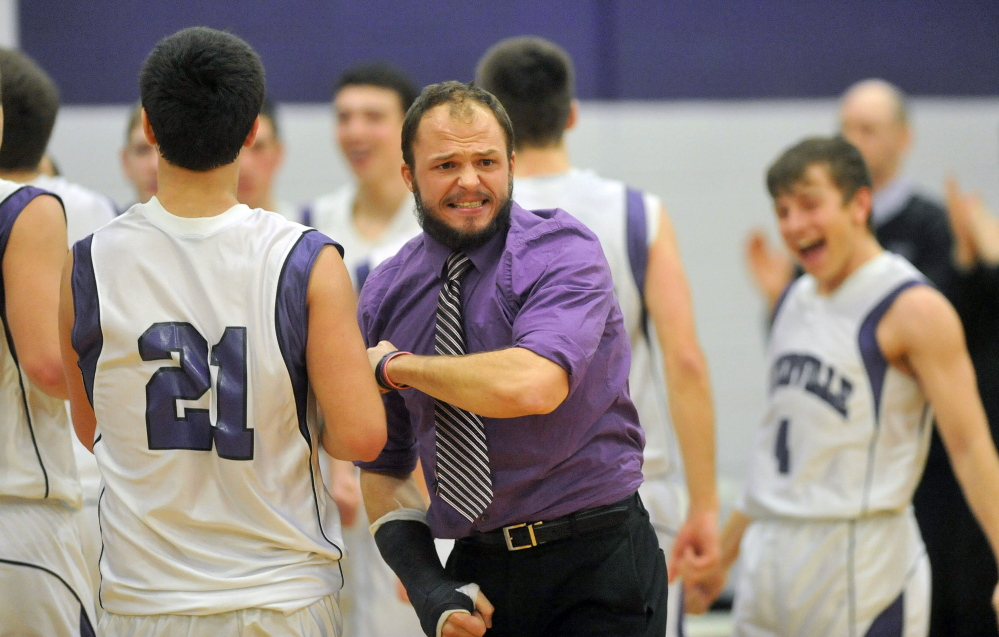 Staff photo by Michael G. Seamans Waterville Senior High School head coach Wade Morrill celebrates with his players after defeating Camden Hills High School 62-56 in Waterville on Friday.