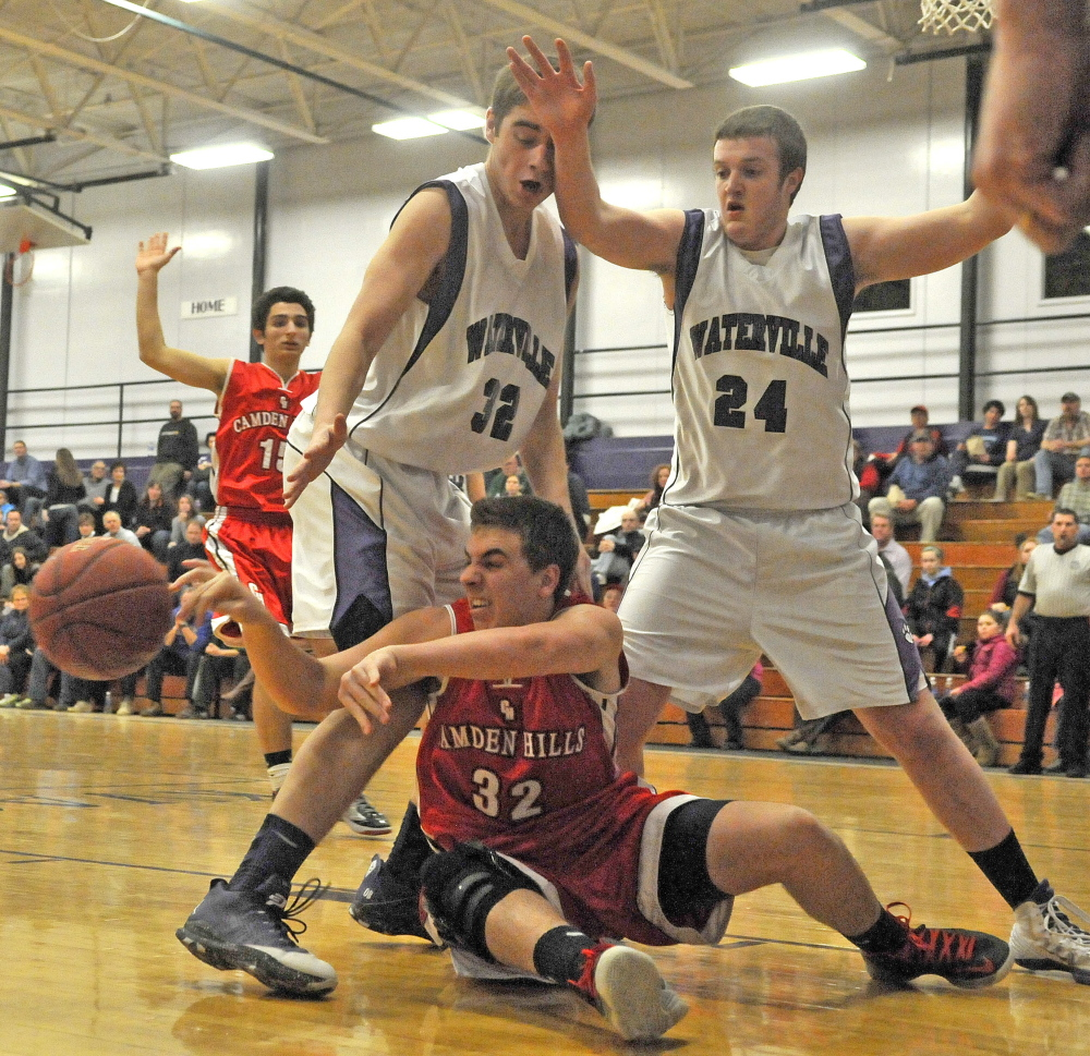 Staff photo by Michael G. Seamans Camden Hills High School's Jayson Kuhn, 32, tries to pas the ball as he is defended by Waterville Senior High School's Owen Brown, 32, and Matthew Bernier, 24, in the second quarter in Waterville on Friday. Waterville defeated Camden Hills 62-56.