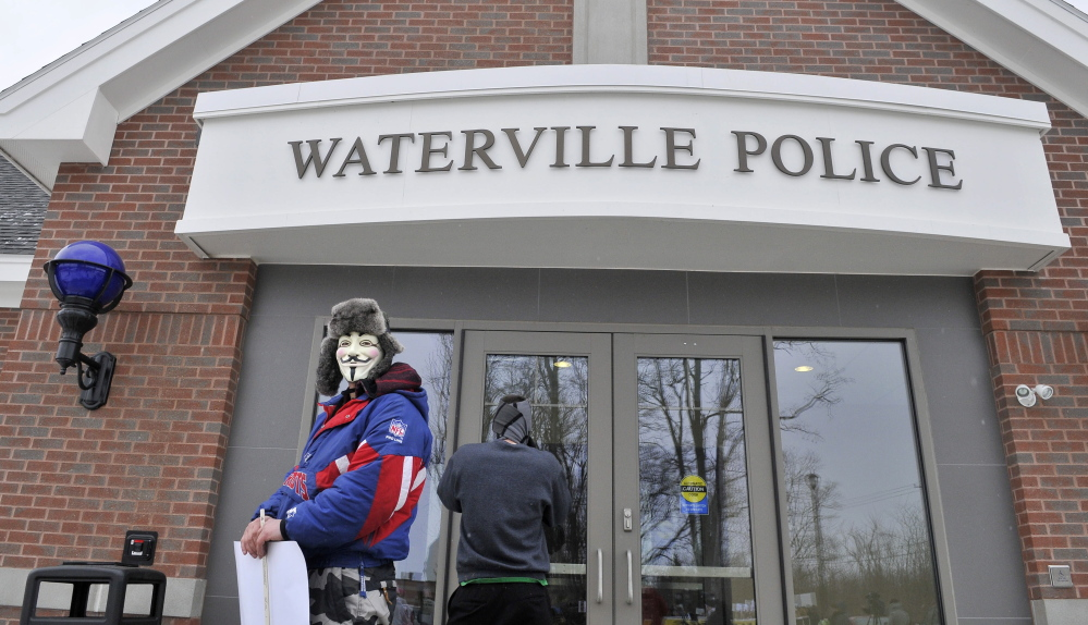 protest: Mark Leighton, of Gardiner, wears a mask Saturday as he takes part in the Push for Prosecution protest in the Ayla Reynolds case at the police station in Waterville.