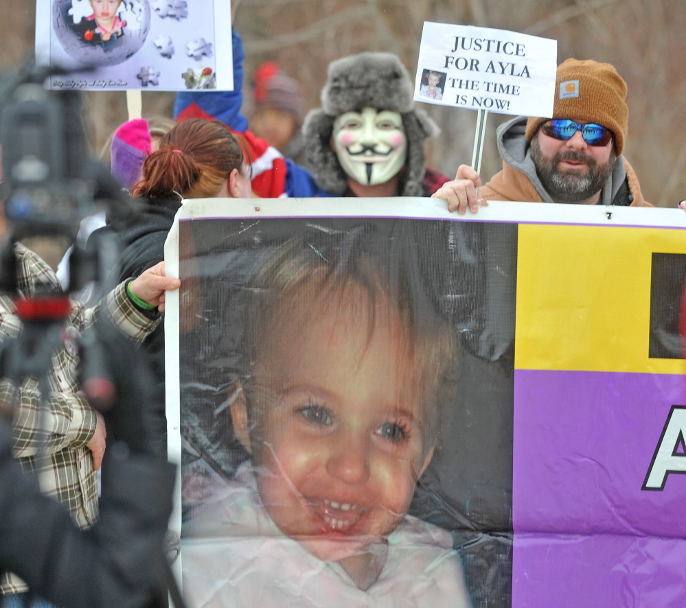 unsolVed: Protesters hold a large sign of missing toddler Ayla Reynolds during a protest about the unsolved case Saturday in Waterville.