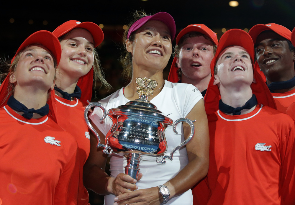 Li Na holds the championship trophy after defeating Dominika Cibulkova in their women's singles final at the Australian Open tennis championship in Melbourne, Australia, on Saturday. She is accompanied by the tournament's ball boys and girls.