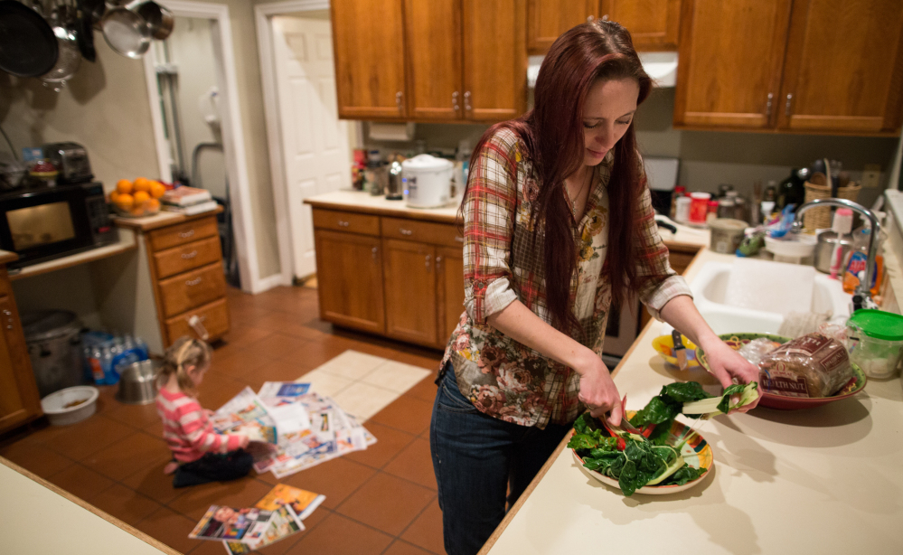 Maggie Barcellano prepares dinner at her father's house in Austin, Texas, on Saturday. Barcellano, who lives with her father, enrolled in the food stamps program to help save up for paramedic training while she works as a home health aide and raises her 3-year-old daughter.