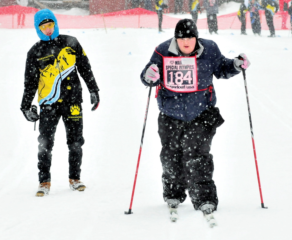 THE RACE IS ON: Caitlin Killarney of Families Matter Inc. in Waterville competes in the 100-meter nordic race during the 45th annual Special Olympics Maine Winter Games at Sugarloaf USA on Monday, Jan. 27, 2014. At left, Colby Watts of Maranacook High School cheers her on.