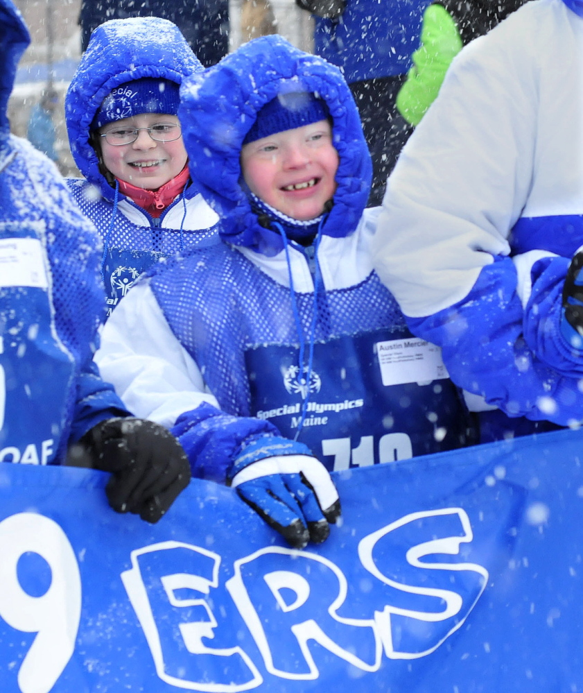 FRIENDLY COMPETITION: Austin Mercier was all smiles as he and other teammates of the Madison 59ers group march in the parade during opening ceremonies of the 45th annual Special Olympics Maine Winter Games at Sugarloaf USA on Monday, Jan. 27, 2014.