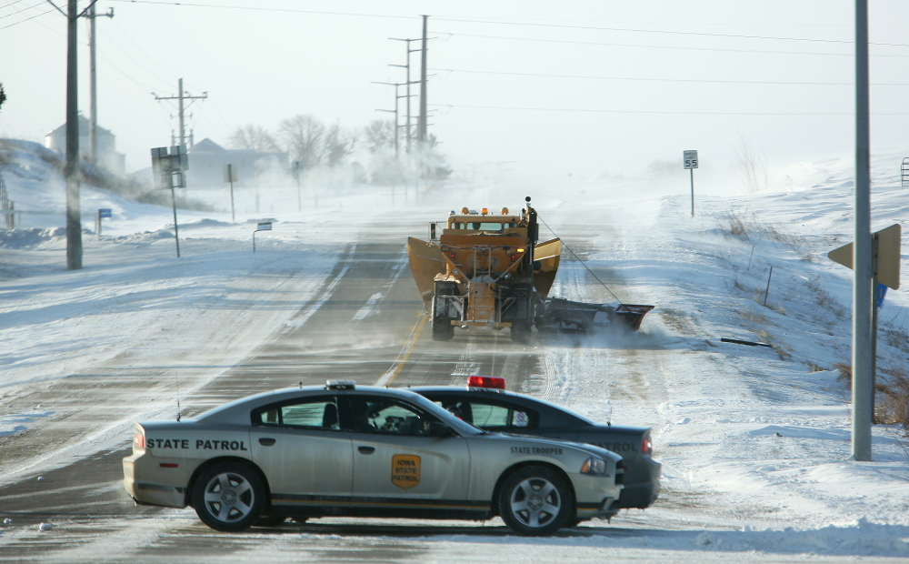 Iowa state patrol officers block Sundown Road going south out of Peosta, Iowa, on Monday due to heavy drifting and blowing snow.