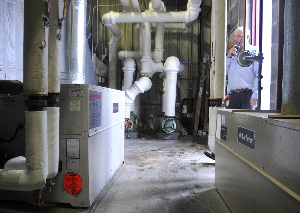 SWITCH: Gary Ford walks through the boiler room at the Augusta Civic Center on Monday, where he works as an electrician. The 18 boilers in the arena are being converted from propane to natural gas, a process that's not as easy or cheap as the city originally hoped.