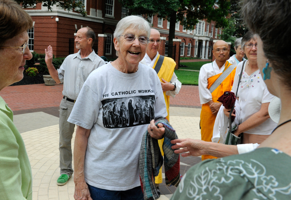 In this Aug. 9, 2012, file photo, Sister Megan Rice, center, and Michael Walli, in the background waving, are greeted by supporters as they arrive for a federal court appearance in Knoxville, Tenn.