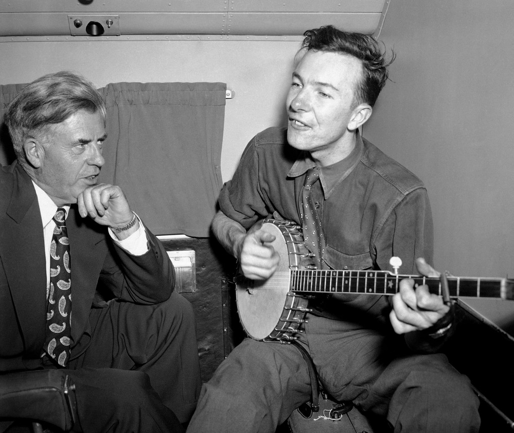 In this Aug. 28, 1948 file photo, Henry A. Wallace, Progressive Party presidential candidate, listens to Pete Seeger on a plane between Norfolk and Richmond, Va. Seeger died on Monday Jan. 27, 2014, at the age of 94.