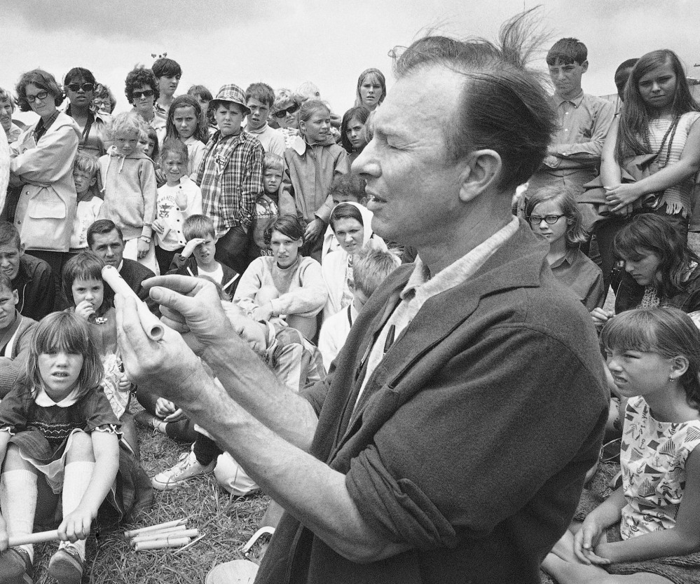 In this 1966 photo, Pete Seeger conducts an instrument making session on Children's Day at the Newport Folk Festival, in Newport, R.I.